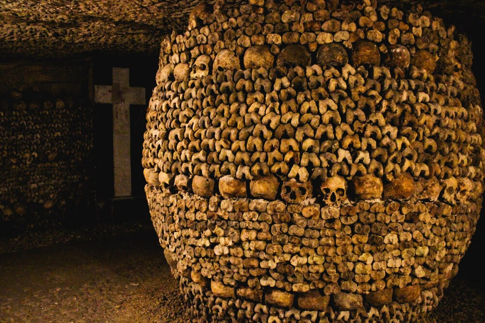 Catacombs of Paris in France. Walls made of skulls and bones.