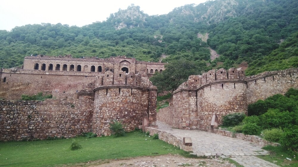 Bhangarh Fort in India. Stone building set into green hillside.
