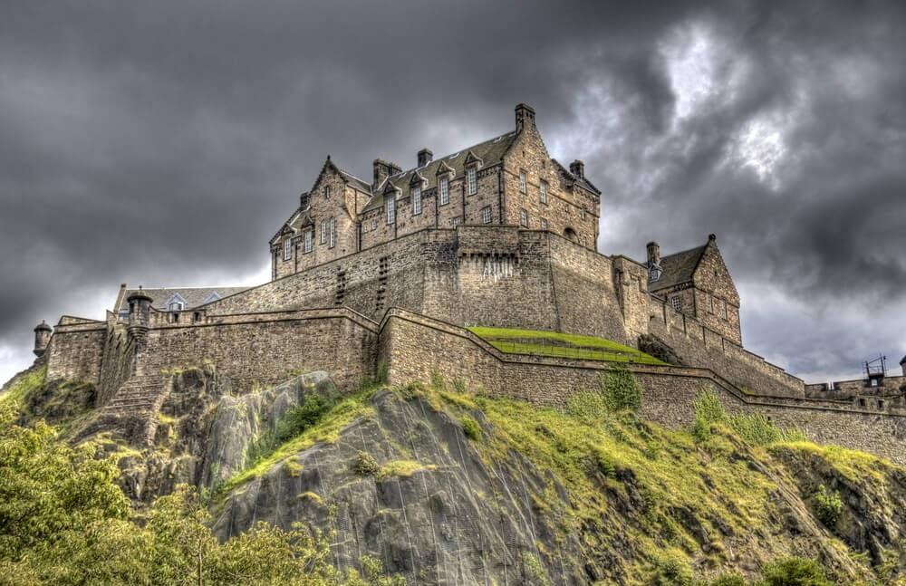 Edinburgh Castle in Scotland photographed from below against a dark grey sky.