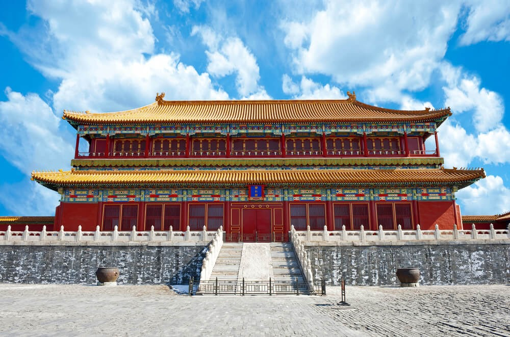 Beijing Forbidden City, China. Large red building with multicolor decoration and a gold roof.