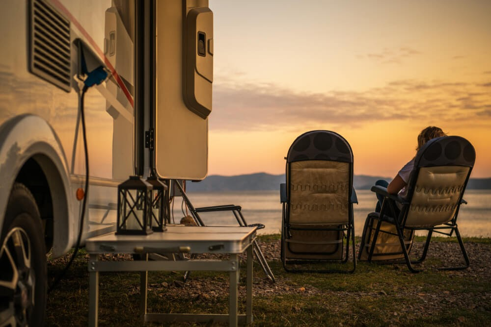 RV at sunset, two camp chairs looking over the water.