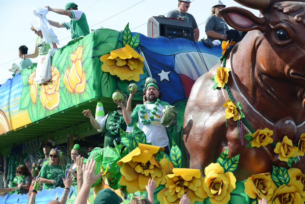 Large double decker parade float of a bull, covered in people wearing green