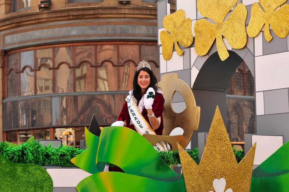 Woman on a shamrock covered parade float wearing a tiara