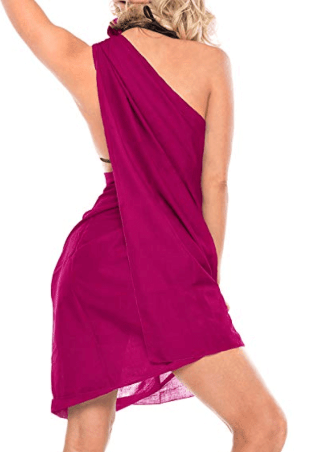 Woman in pink sarong model one shoulder style wrap, from behind.  tie
