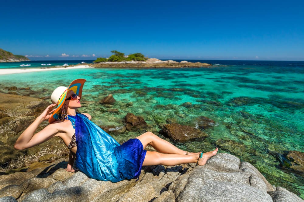 Woman in sarong and sunhat lay on beach with beautiful clear blue water surrounding her.