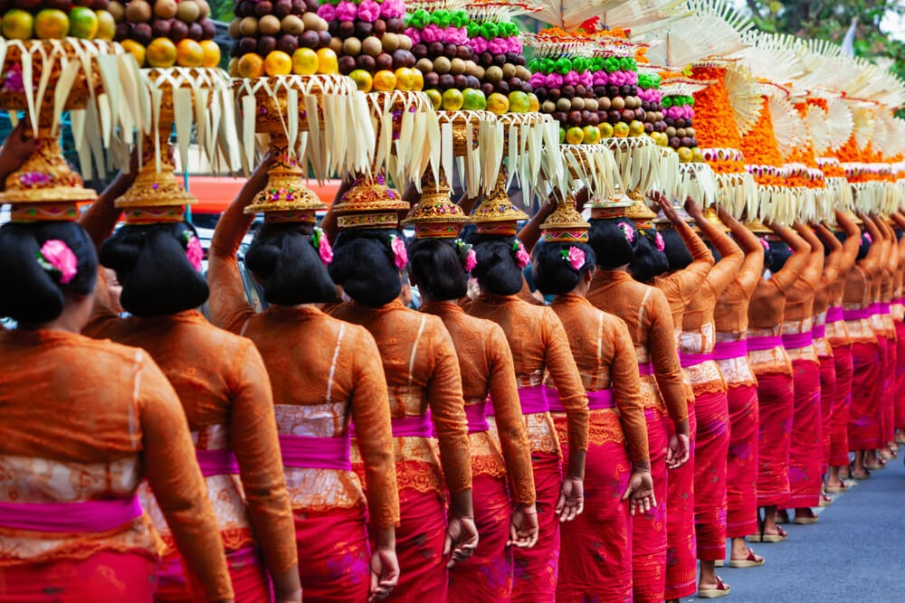 Photo of a line of women from behind in brightly colored clothes and sarongs. They are holding elaborate headpieces with various fruits and nuts