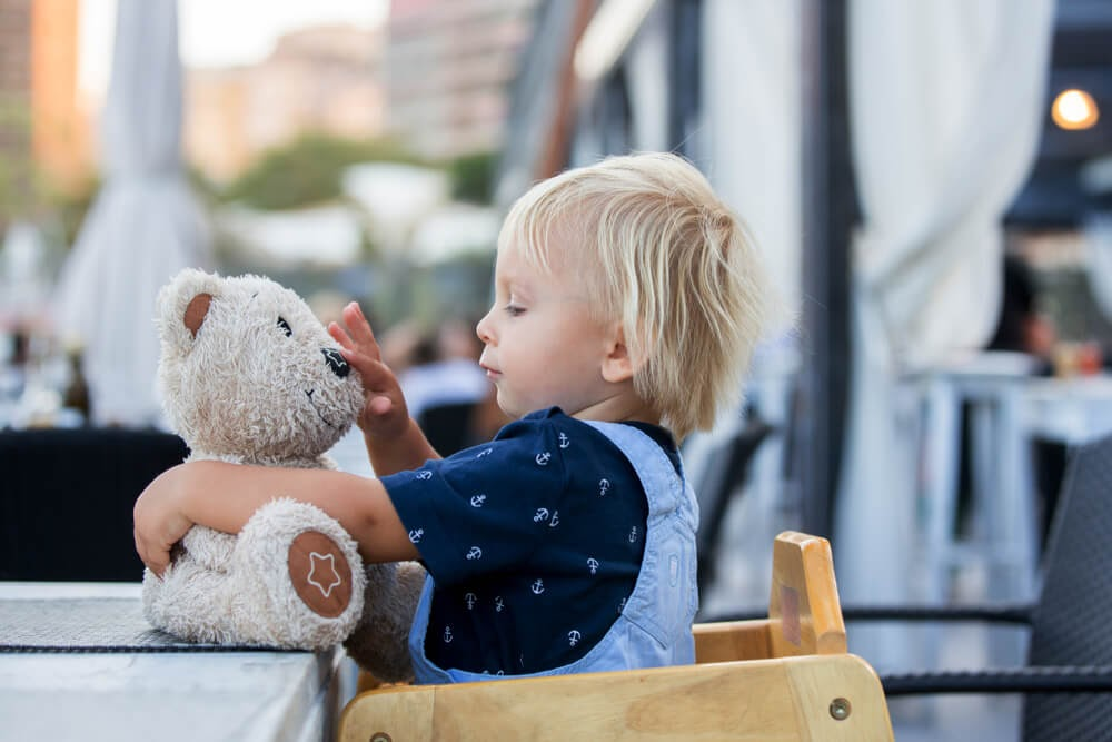 Toddler in restaurant highchair with stuffed bear.