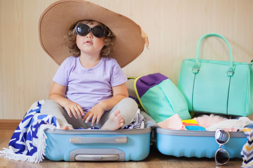 Toddler sits in packed suitcase wearings sunglasses and a big straw hat