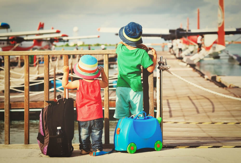 Two small toddlers look out at water planes with their suitcases. Photo is from behind.