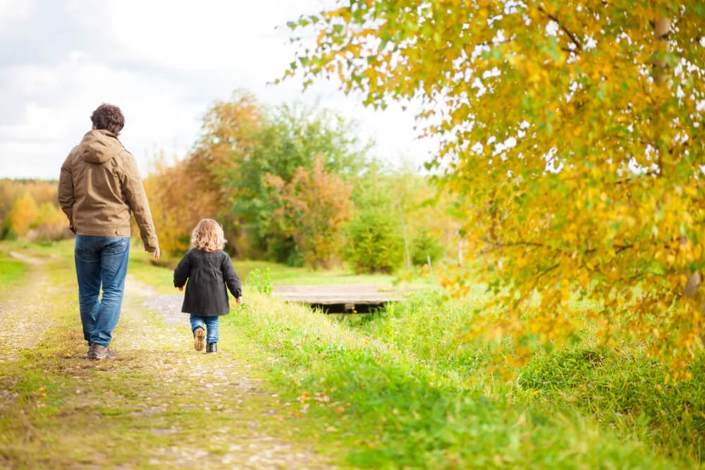 Man and small child walking through yellow and green trees on a grassy path.