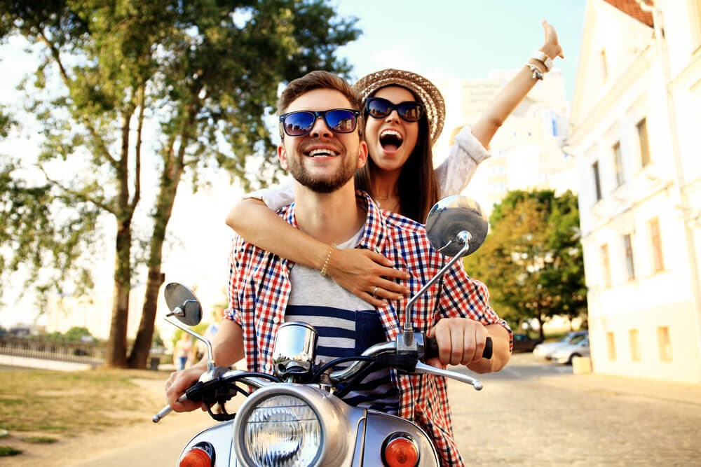 Young couple ride on small motor cycle. Woman holds onto man from behind and smiles with one of her arms in the air.