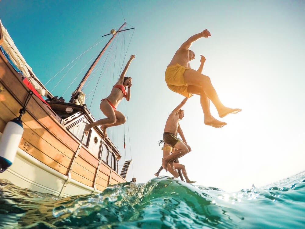 Group of yound people jumping into the ocean from a large sailboat. Photo is taken from below and the sun is shining into the camera.
