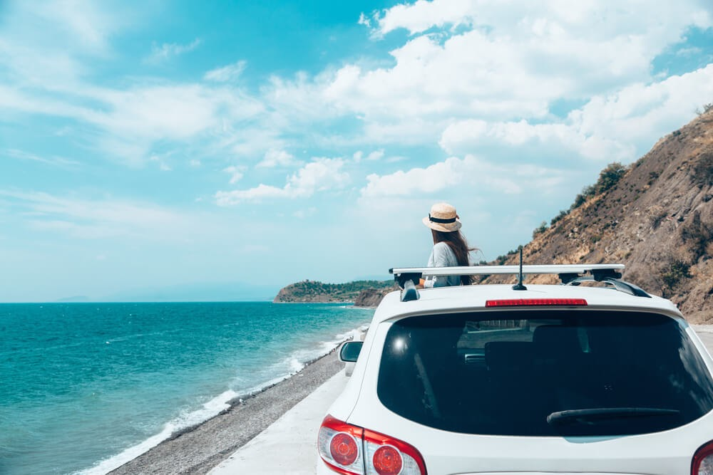 Woman standing in front of a white car along a coastal road. The sky is blue and the wind is blowing through her hair.