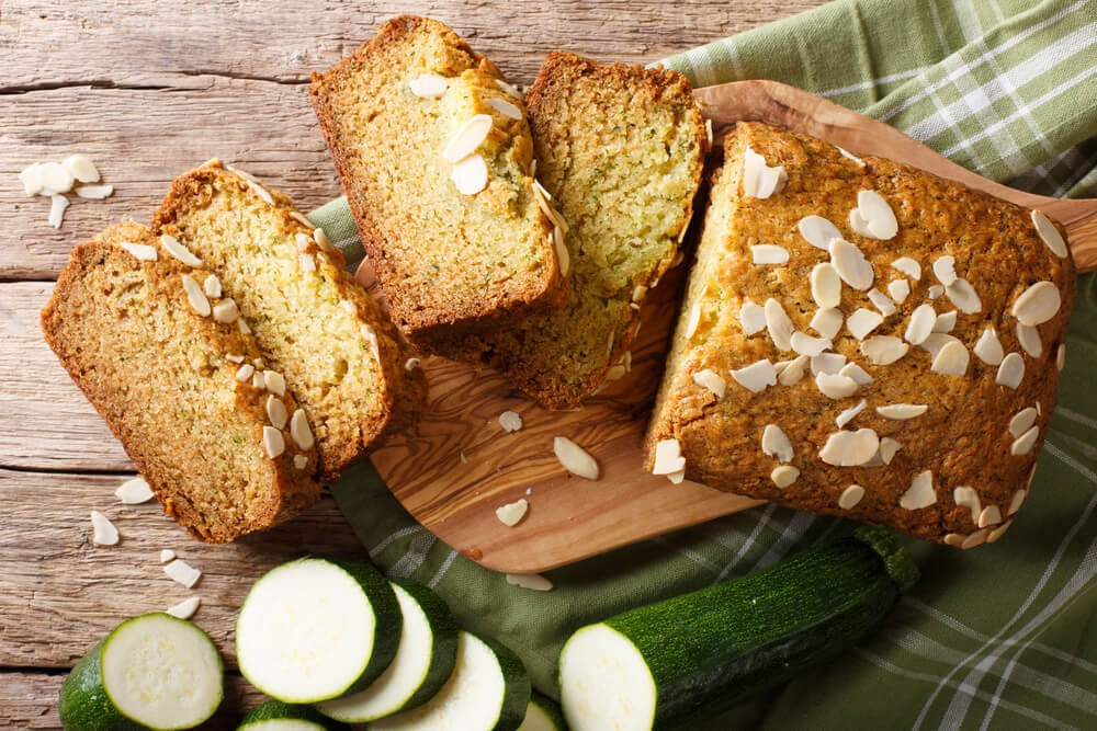 Loaf of zucchini bread with nuts. A sliced zucchini sits next to the sliced loaf.