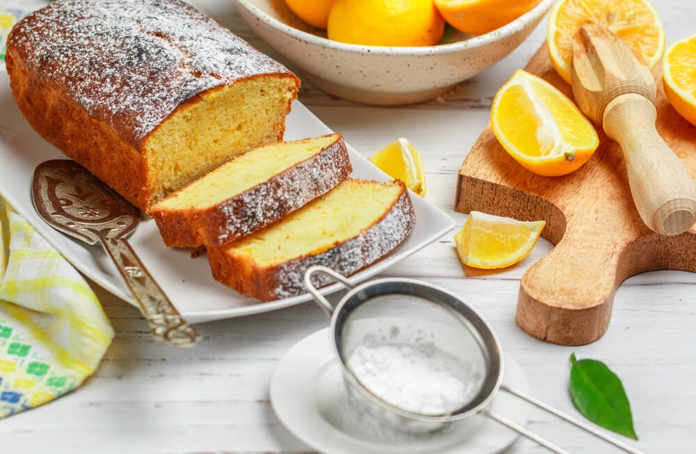 Sliced loaf of lemon bread dusted with powered sugar. A bowl of lemons and s few lemon wedges sit next to the loaf.