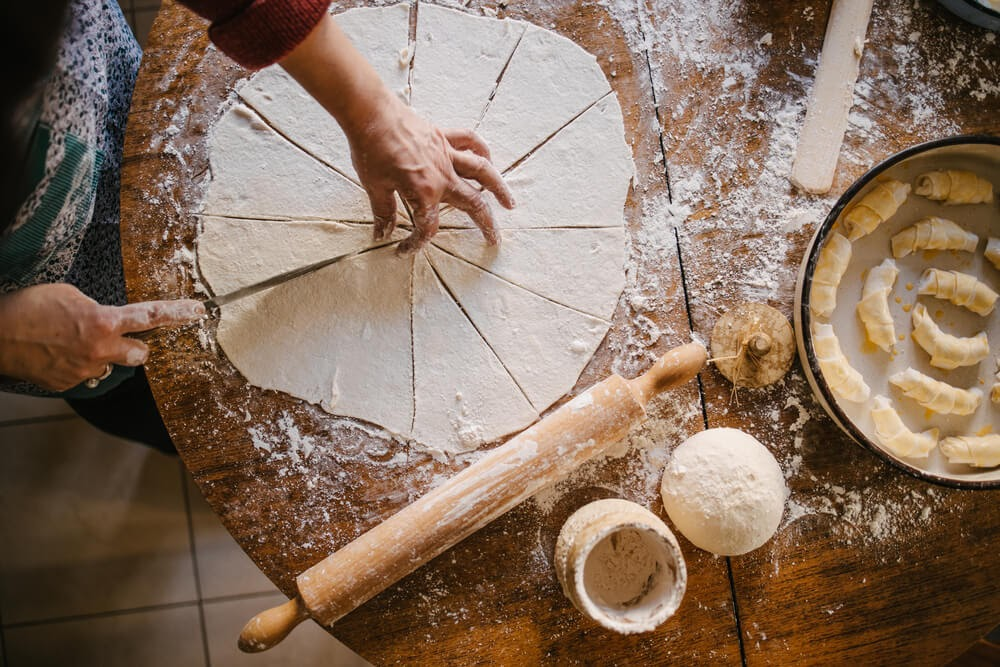Overhead shot of person working with dough on a board. A round piece has been thinly rolled and is cut into pie shaped pieces.