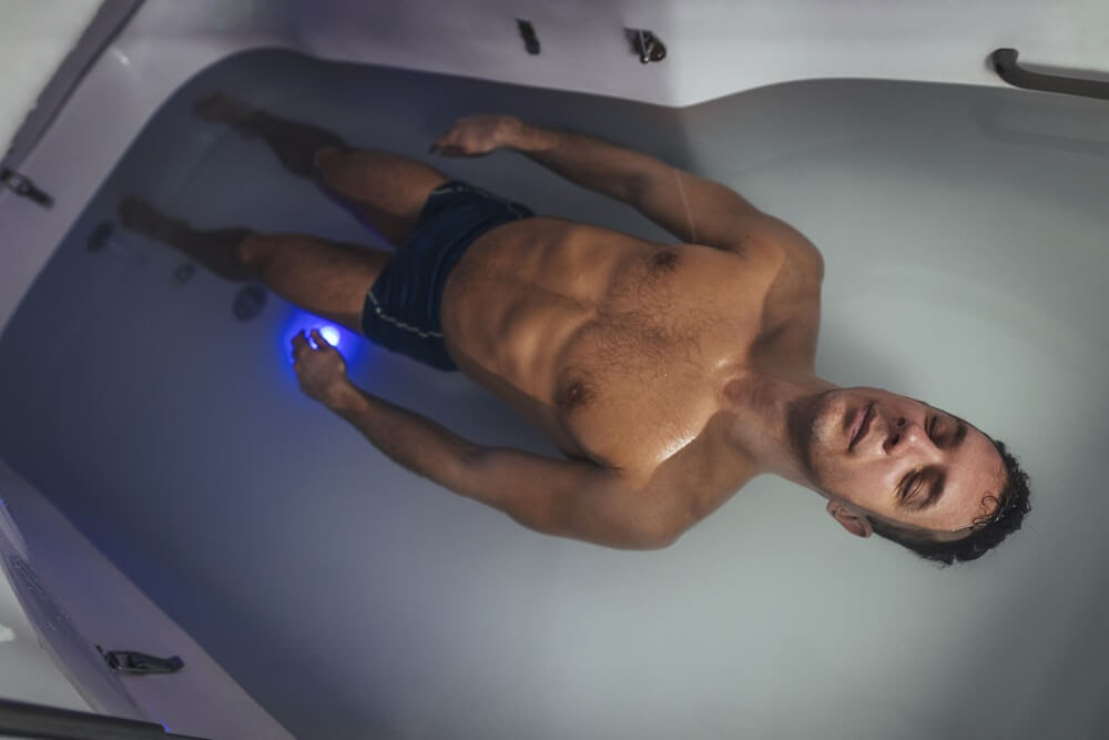 Man floating in deprivation tank with his eyes closed.