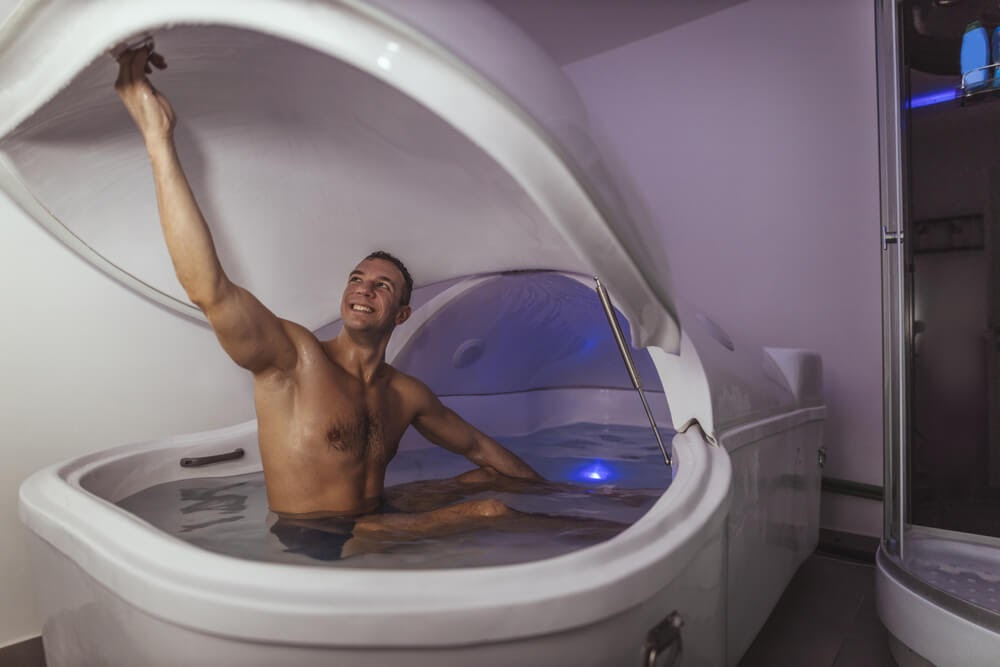 Man smiling while he gets into a floating deprivation tank.