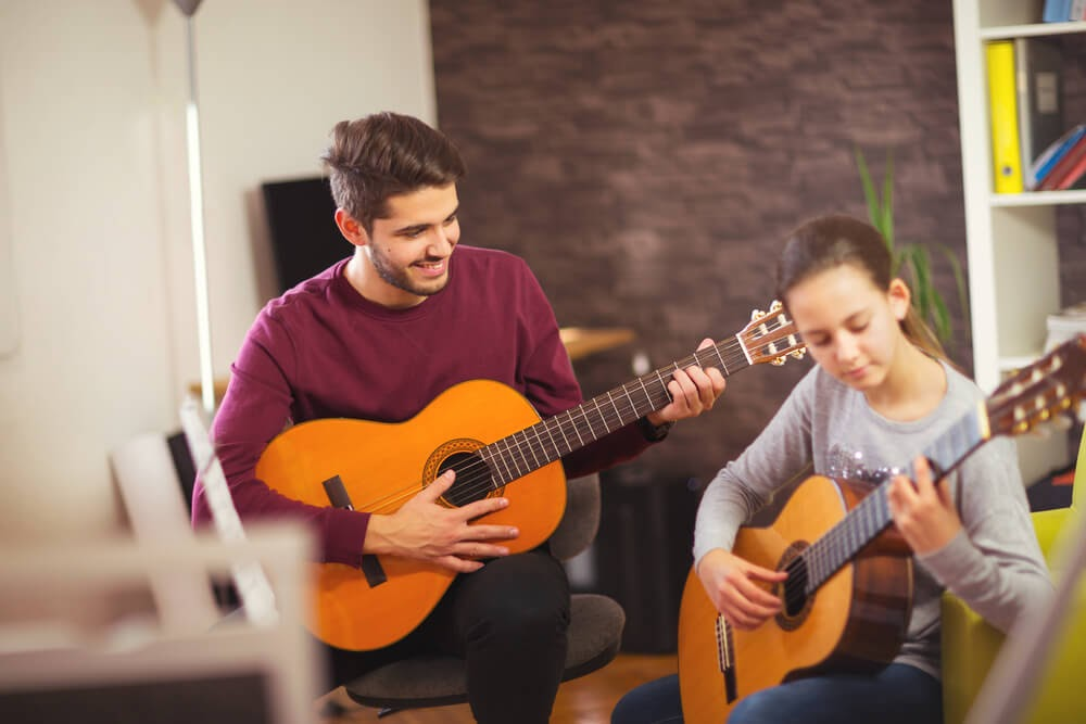 Two people playing guitar.
