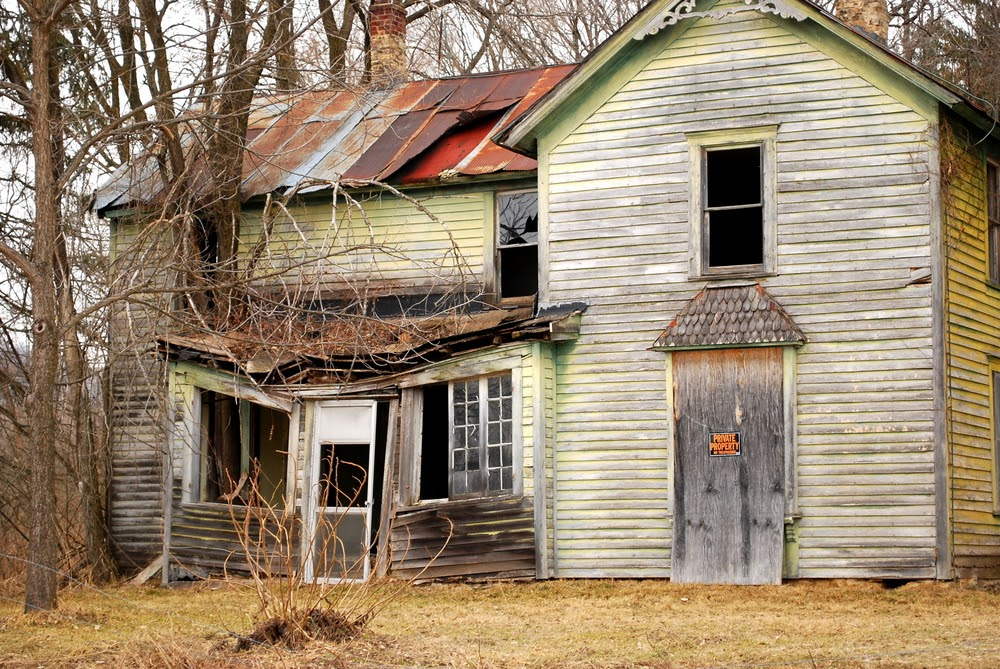 A dilapidated old house with a caved in roof and a private property sign