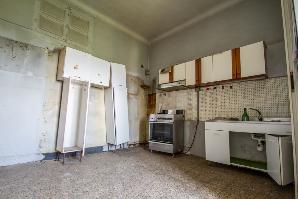 A kitchen that has been stripped and needs repair