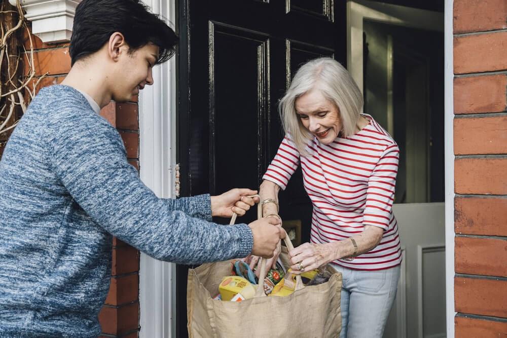 teenage boy delivering groceries to elderly woman