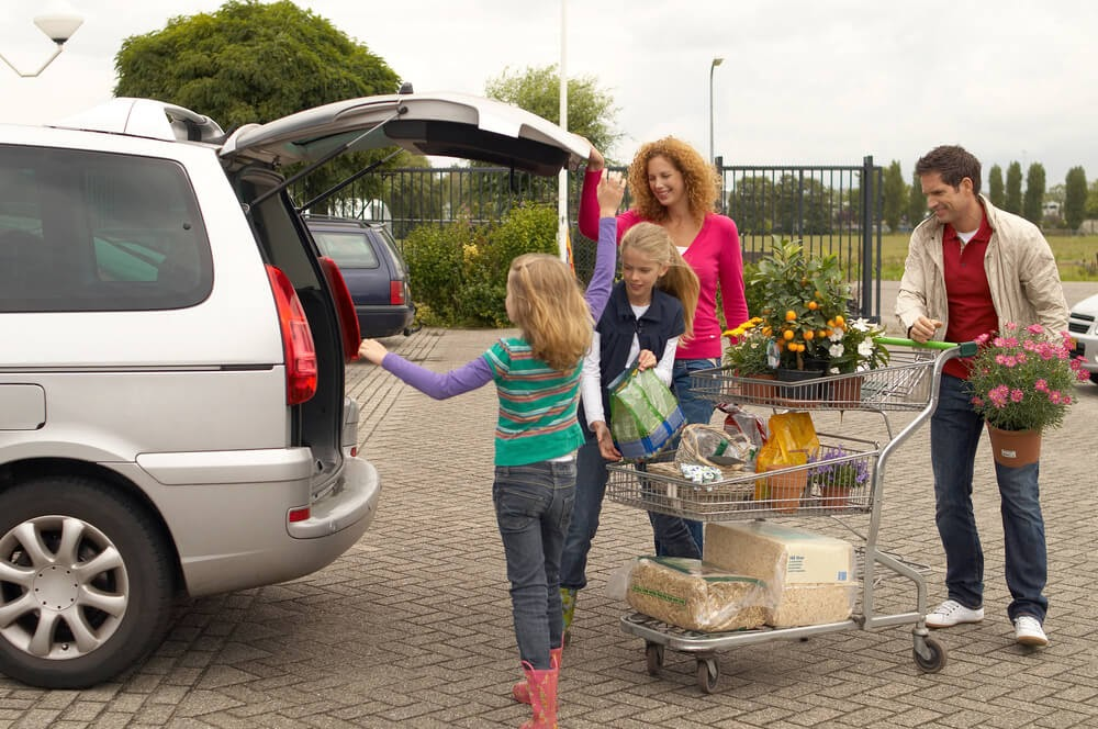 Family loading the trunk of their car with plants and garden supplies.