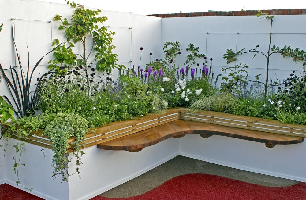 Raised corner bed with flowers in purple tones.