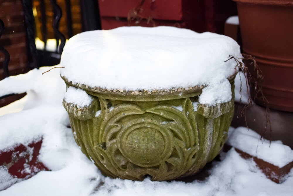 Decorative pot covered in snow.
