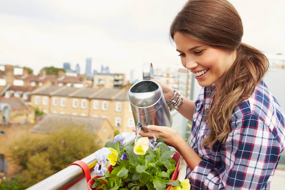 Young woman smiling while watering plants with a silver watering can.