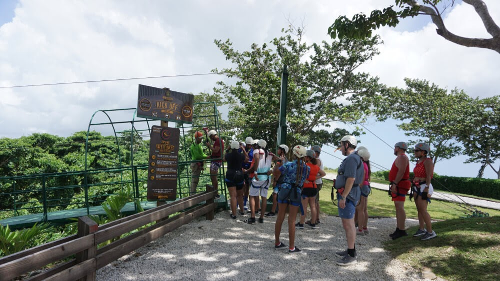 Tourists stand in line with helmets and harnesses on.