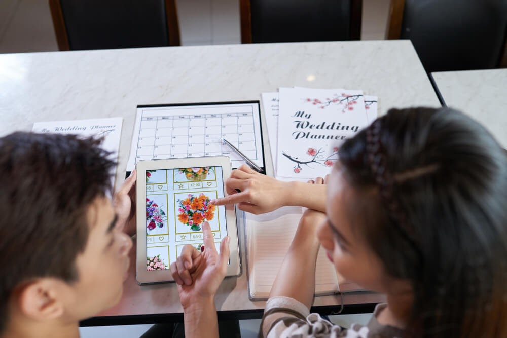 Couple looks at a tablet showing multiple floral displays.