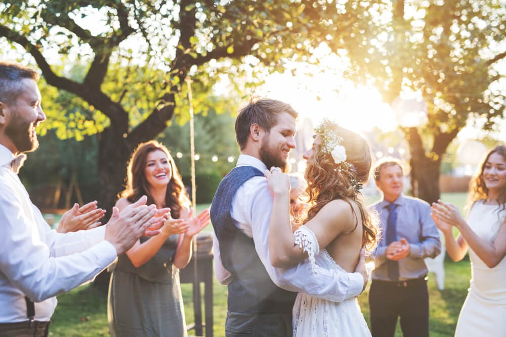 Couple dancing in wedding attire. The sun is shining and everyone is smiling