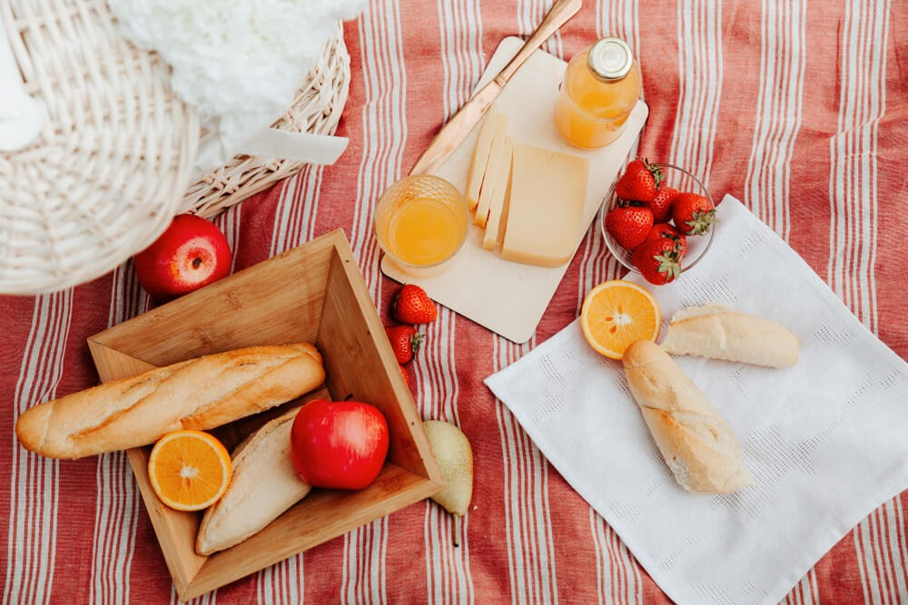 Picnic image with bread, cheese, fruit and juice.