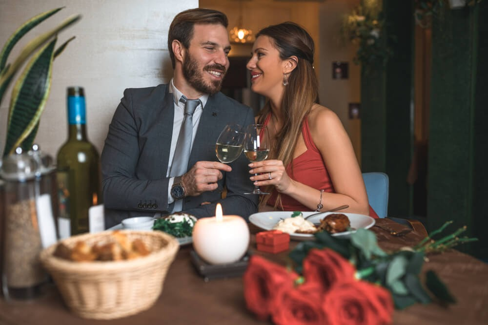 A couple dressed up nicely and toast each other with wine glasses