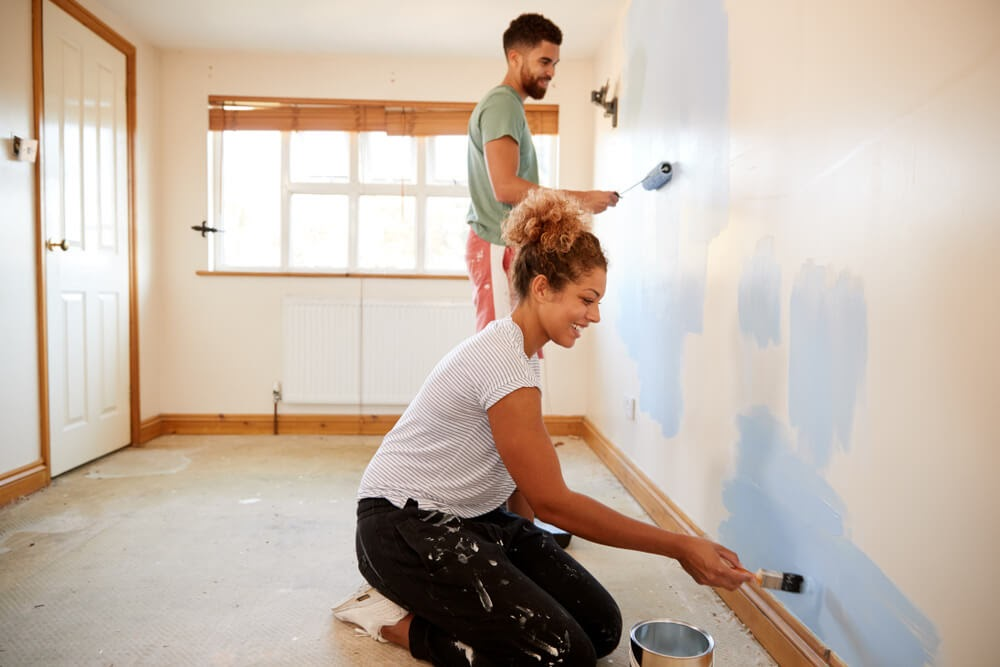 Man and woman painting a yellow room blue.