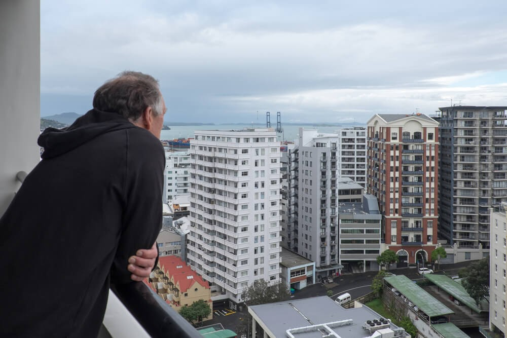 Man looks over city from balcony.