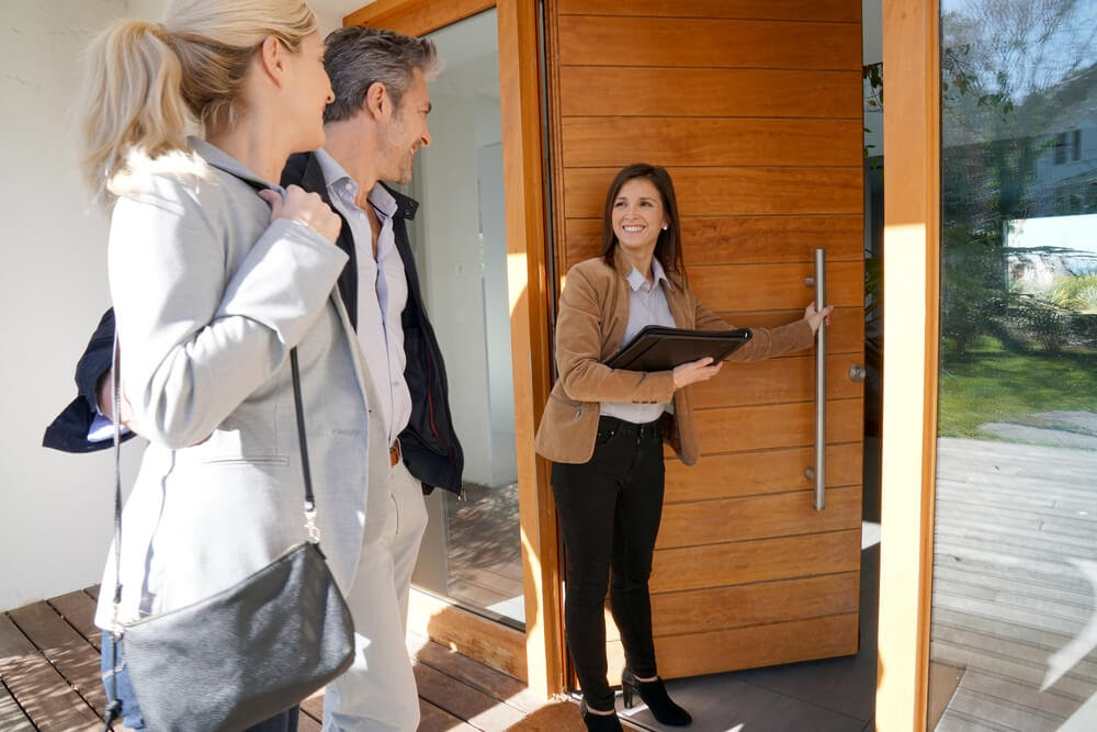 Realtor opens door for couple. They are all smiling at each other.