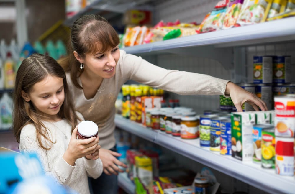 Woman and small child buying canned foods in a store.