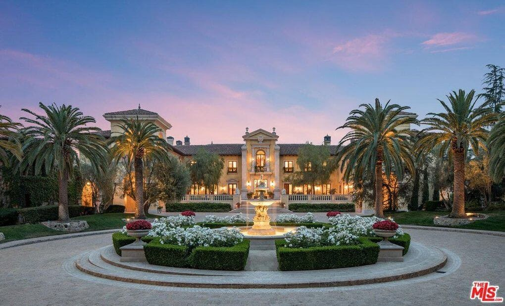 67 Beverly Park Court, a massive Hollywood mansion with a beautiful sunset in the background.