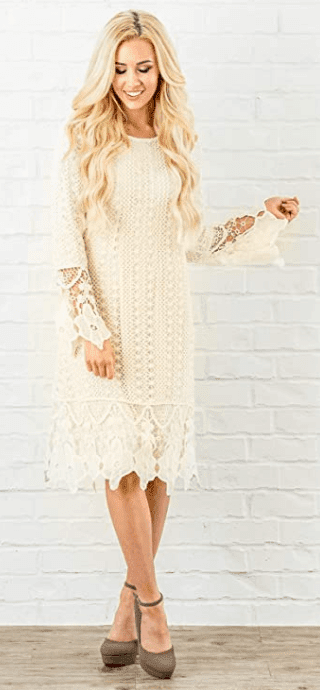 White crochet dress on blonde model standing in front on a white brick wall.