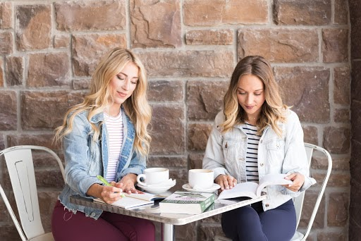 Two women sit at a table with a mugs and books.