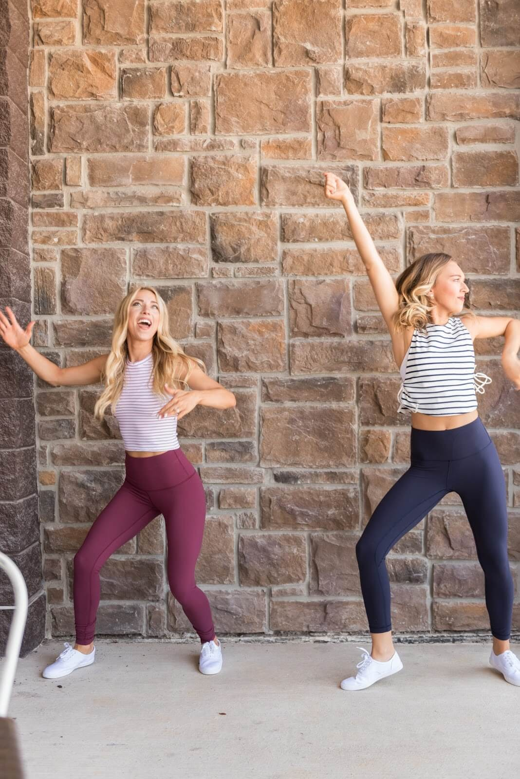 Two women dancing in front of a brick wall.