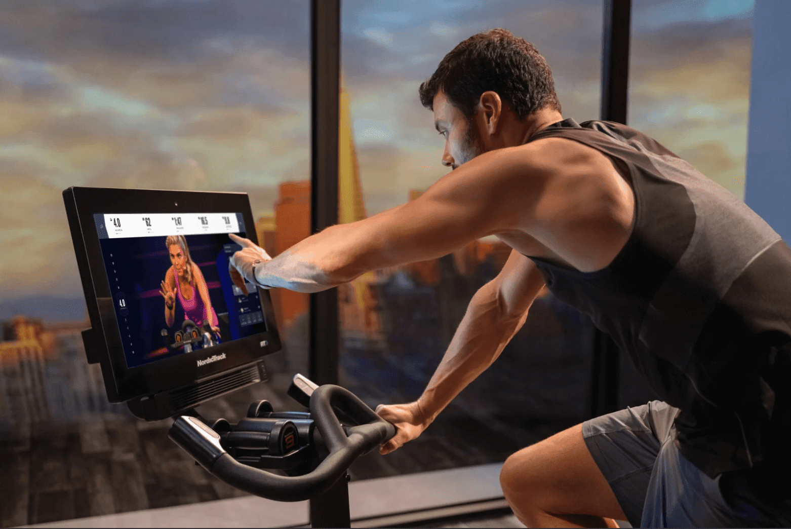 Man on exercise bike with digital screen.