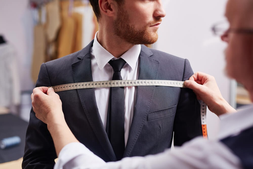 Man in suit being measured across his chest.