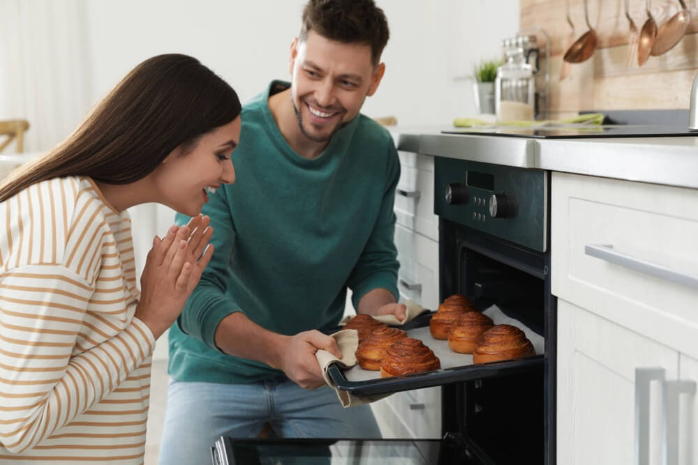 Man pulling cinnamon rolls out of the oven and a very happy woman looks on.