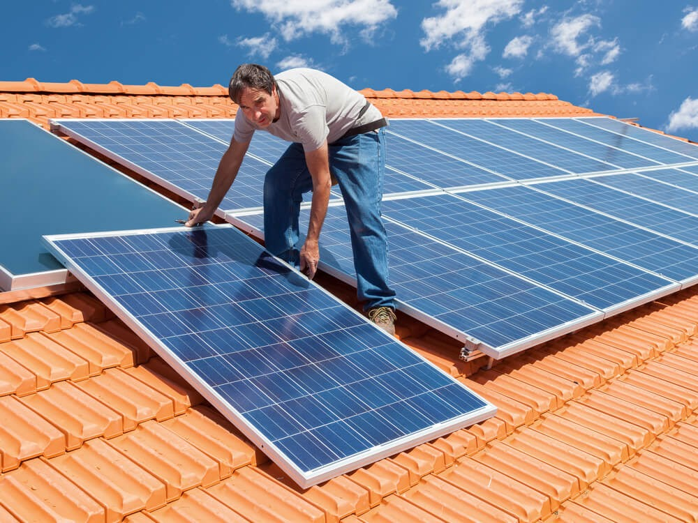 Man on a roof top installing solar panels.
