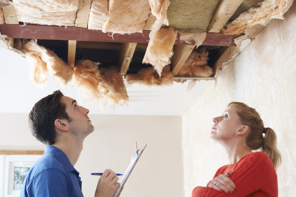 Two people look up at a damaged ceiling.