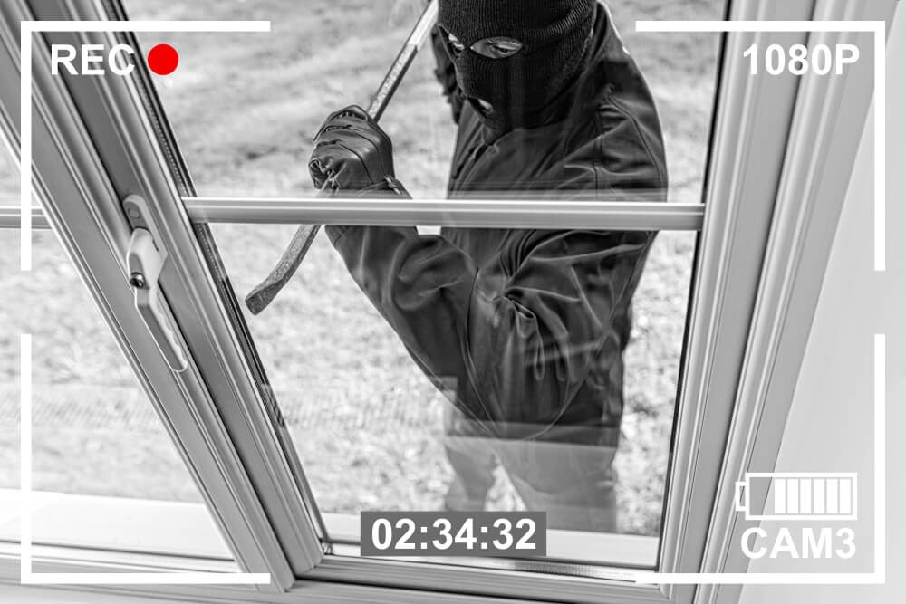 Security footage of a break-in. Perpetrator has on a black ski mask and uses a crowbar.