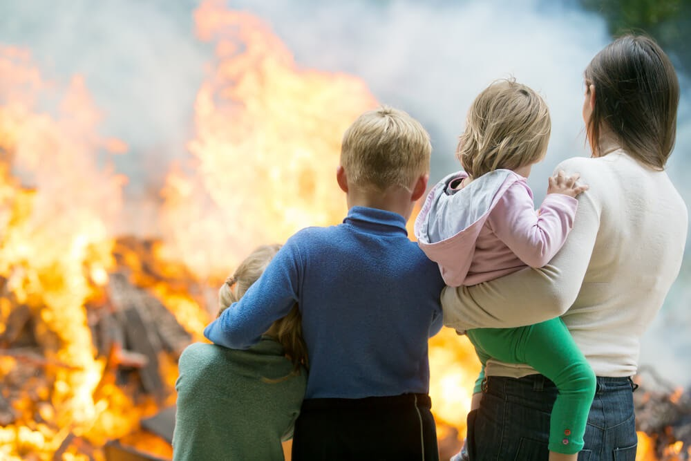 Family looks onto large fire.